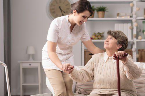 una signora anziana seduta su un divano e una donna accanto che tiene la mano