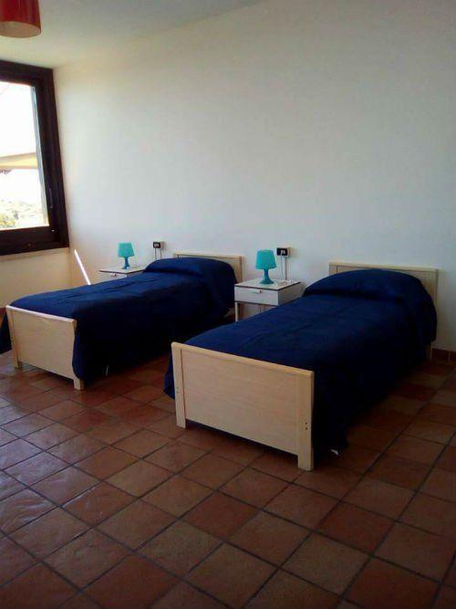 una stanza con due letti singoli e due comodini