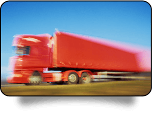 Blurred image of a red lorry travelling at speed.