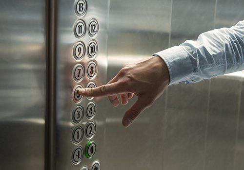 una mano che preme un tasto di un ascensore