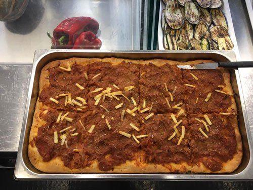 una pizza in teglia con solo pomodoro e delle fettine di formaggio