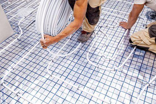 operai installano un sistema idraulico per riscaldamento a pavimento