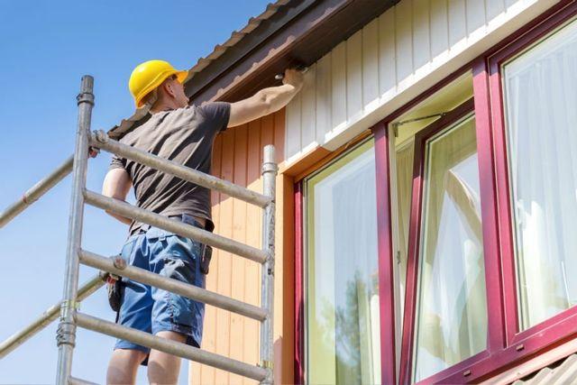 Lavoratore imbiancando la parete della casa
