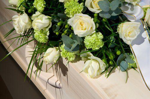 Composizione floreale bianco-verde su una bara