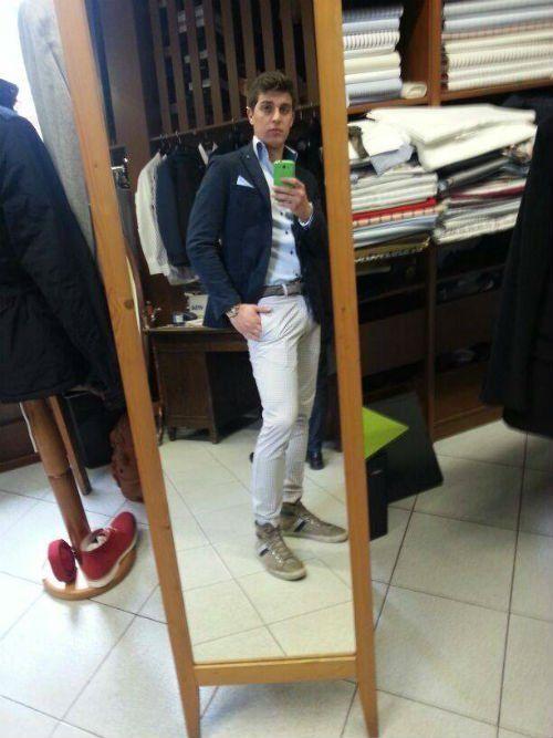 un uomo con dei pantaloni di color bianco e un giacca di color blu