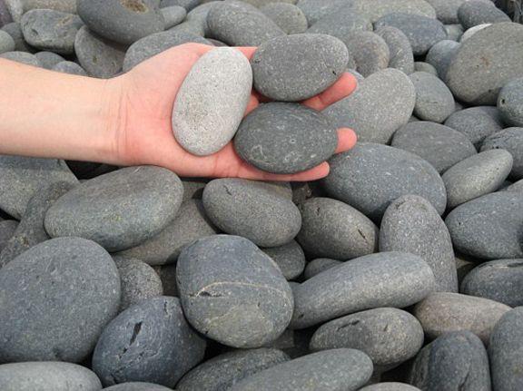 Hand Holding Basalt River Rock