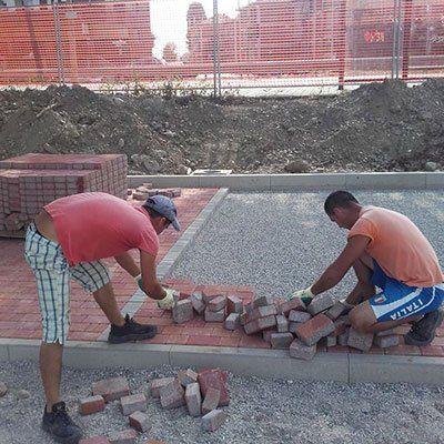 dei muratori che sistemano dei mattoni
