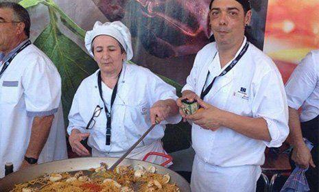 Una cuoca mentre cucina un piatto di pesce in una padella grande e di fianco un altro cuoco che sorride