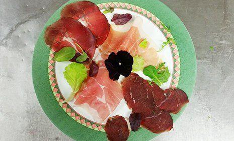 Un piatto con salumi e foglie di insalata mista