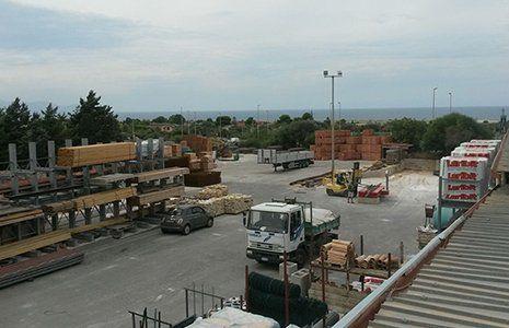 un parcheggio con delle macchine, un camion, assi di legno e del materiale edile