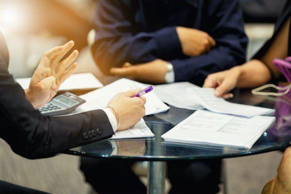 tre persone sedute intorno ad un tavolo rotondo, che discutono davanti a dei documenti assicurativi