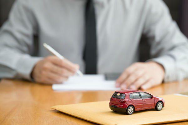 un uomo in camicia e cravatta, seduto ad un tavolo, che scrive su un foglio ed in primo piano il modellino di una macchina rossa