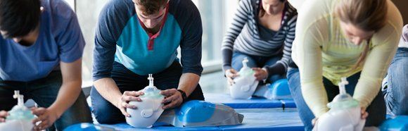 People practising CPR on dummies