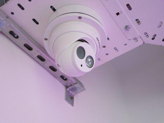 A CCTV camera near an escalator in a commercial building
