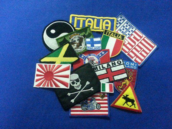 degli stemmi da cucire raffiguranti delle bandiere di diverse località
