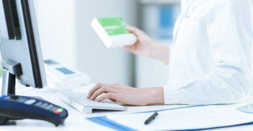 Farmacista al PC con confezione di farmaci in mano