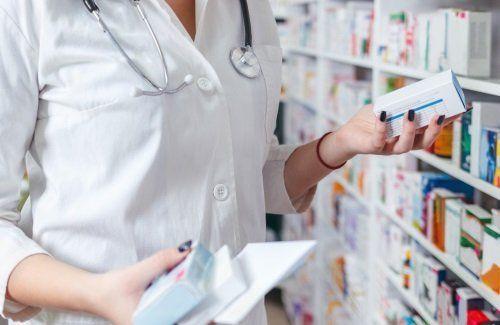 Una farmacista con confezioni di farmaci in mano