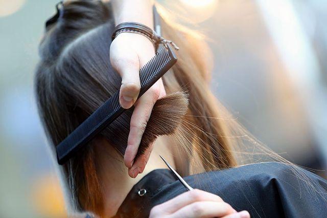 una mano di una parrucchiera che tiene un pettine e i capelli di una ragazza
