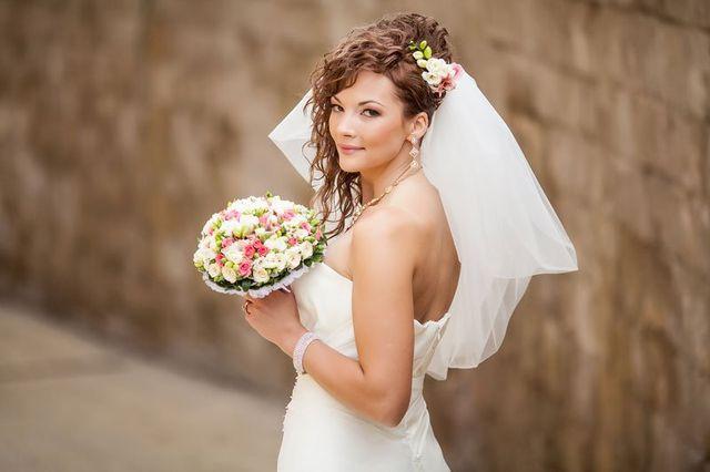 una ragazza vestita da sposa con un bouquet di fiori in mano