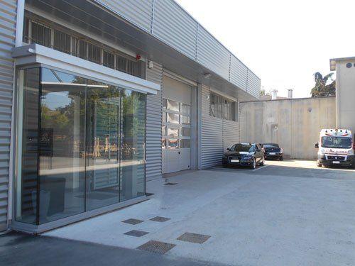 un ingresso a uno stabile con una porta in vetro e delle macchine parcheggiate