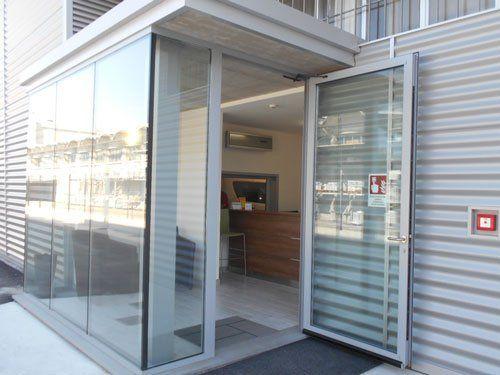 un entrata con porta in vetro con vista di un bancone in legno