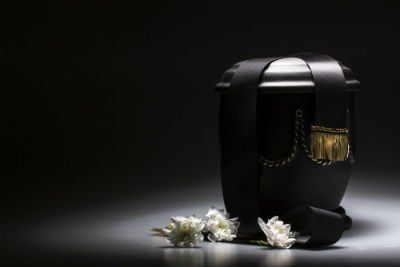 Urna nera con dettaglio dorato e fiori bianche