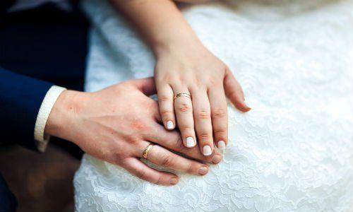 Le mani di due sposi novelli indossando le alleanze