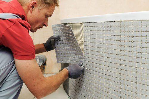 un operaio che posiziona dei rivestimenti su del cemento fresco