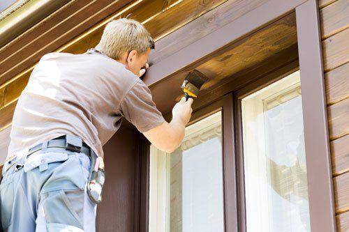 un uomo che con un pennello dipinge una finestra