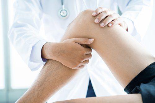 medico tocca il ginocchio a un paziente