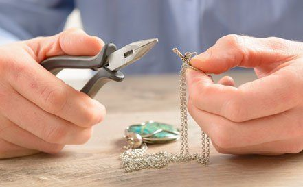 Man repairing silver chain with pliers