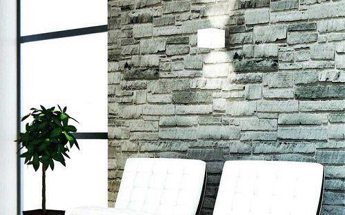 un'applique su un muro in pietra, due sedie bianche e un vaso con una pianta