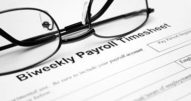 Pair of glasses on a Biweekly Payroll Time Sheet