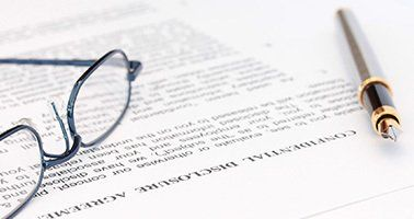 A pair of glasses on a Disclosure Agreement