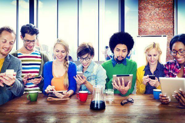 un gruppo di persone sedute a  un tavolo con dei tablet e degli smartphone in mano
