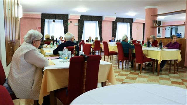 delle persone anziane sedute a dei tavoli in un ristorante