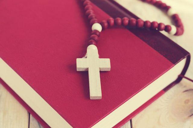un rosario sopra a un libro bordeaux