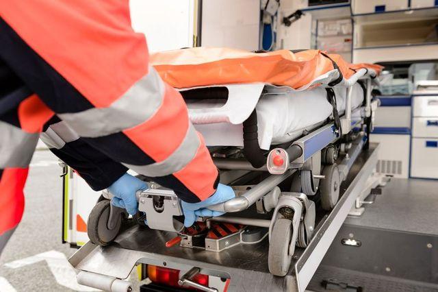 un uomo che mette una barella in un'ambulanza