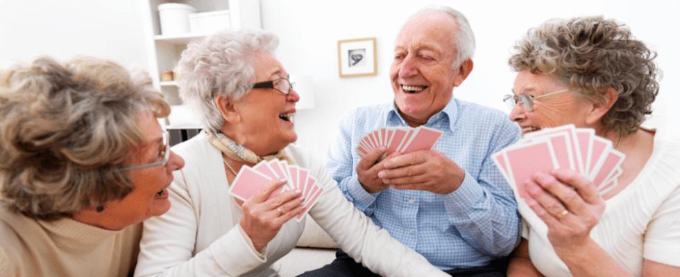Anziani che giocano a carte ridendo