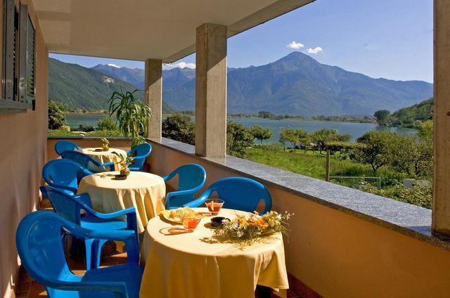 un balcone con tre tavoli e vista del lago