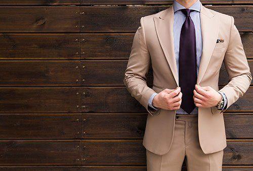 Completo di colore beige, camicia blu e cravatta lilla