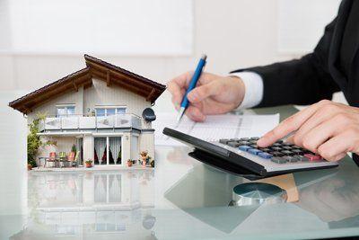 agente fa dei conti con la calcolatrice vicino a un modellino di casa