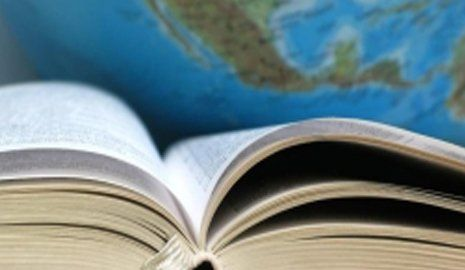 libro aperto vicino a un mappamondo
