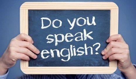 persona tiene in mano una lavagna con scritto Do you speak english?