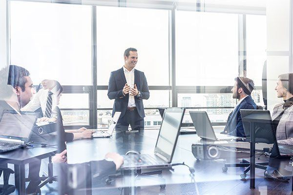 un uomo in piedi e delle persone sedute alla scrivania