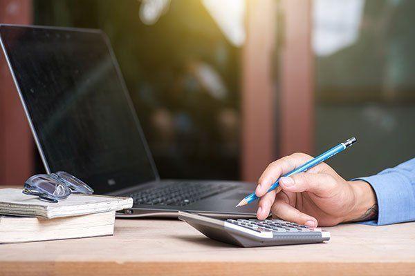 una mano con una penna e davanti una calcolatrice