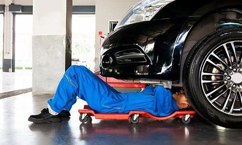 Meccanico in uniforme blu sdraiato e lavorando sotto auto al garage auto