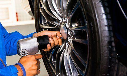 Avvitando meccanicamente o svitando la ruota dell'auto al garage di servizio