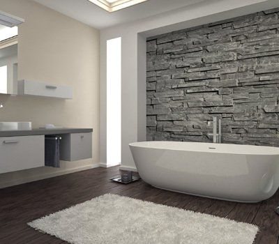 A white rug on a wooden floor alongside a white bath in front of a grey stone-effect wall