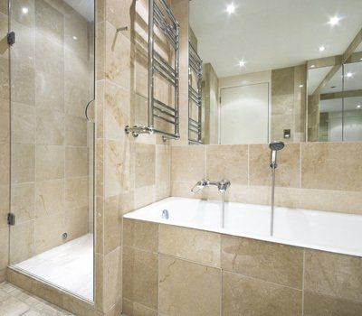 Bathroom with marble effect wall and floor tiles, and shower stall behind the bath